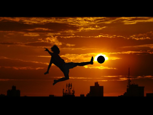 Man Kicking Ball Against Autumn Sky